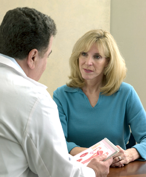 Woman sitting at table, talking to doctor.