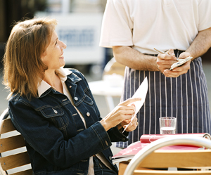 Woman ordering food in an outdoor cafe.