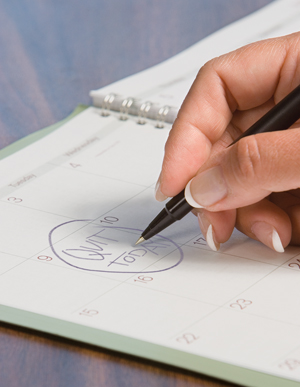"Woman writing in day planner calendar ""Quit today""."
