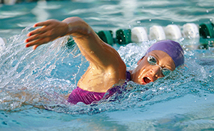 Woman lap swimming in pool wearing goggles and swim cap.