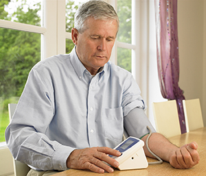 Mature man taking his blood pressure at home.