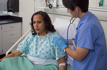 Health care provider listening to the lungs of a woman in hospital bed.