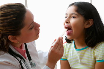 Doctor looking at girl's throat