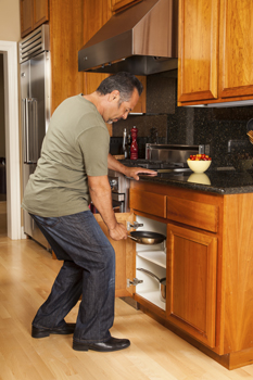 Man bending at knees to retrieve a pan from a lower cabinet.