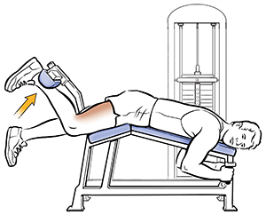 Man doing hamstring curls on exercise machine.
