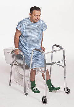 Man in hospital gown in bathroom holding onto toilet side rails to help steady him while he sits on toilet.