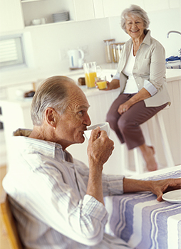 Senior man drinking tea. His wife is drinking orange juice and smiling at him.