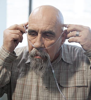 Man putting on a nasal cannula.