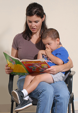 Woman holding boy on lap, reading to him.