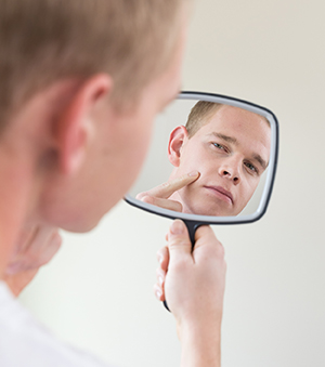 Man looking in hand mirror.