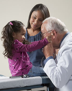 Healthcare provider playing with stethoscope with toddler girl while woman looks on.