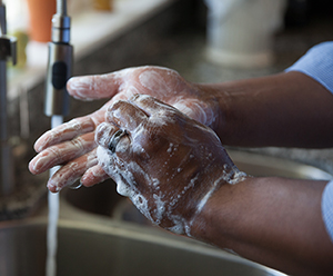 Closeup of hands in sink with running water. Hands are covered with soap suds.