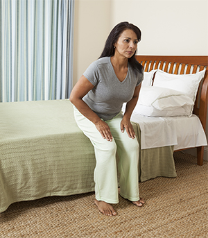 Woman sitting at edge of bed getting ready to stand up.