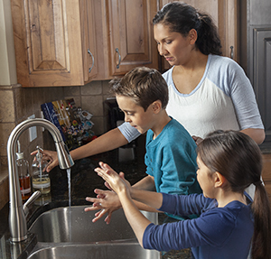 Woman helping boy and girl wash hands in kitchen sink.