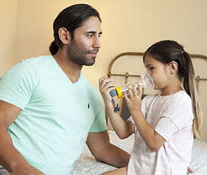 Man helping girl use metered-dose inhaler with spacer and mask.