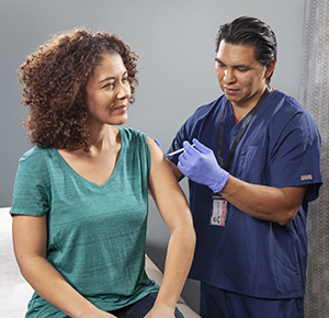Healthcare provider giving woman injection in arm.