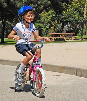 girl riding bike wearing helmet
