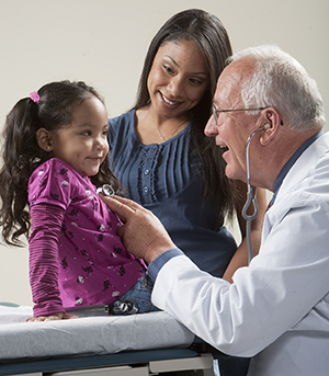 Healthcare provider listening to girl's chest with stethoscope while woman looks on.