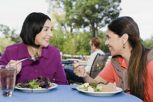Women eating salad in outdoor restaurant.