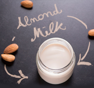 Jar of almond milk, a few almonds, and the words Almond Milk in script on a table