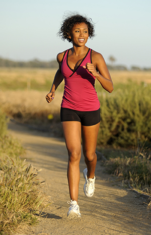 Young woman jogging on dirt path.