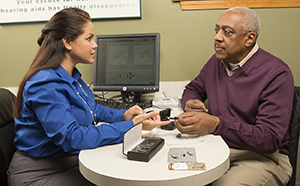 Healthcare provider and man having a hearing aid consultation.