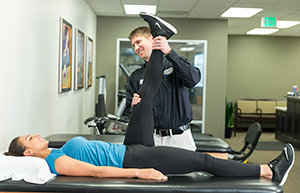 Physical therapist working with woman on leg stretches.