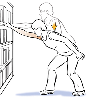 Woman doing shoulder elevation exercise, holding onto bookcase.