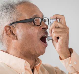 Older man using an inhaler