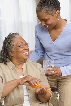 Woman handing glass of water to older woman to take her medicine.