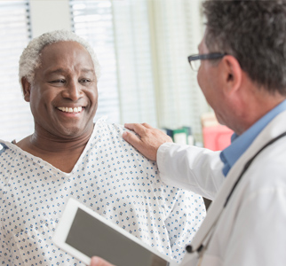 Doctor talking with older male patient in hospital gown