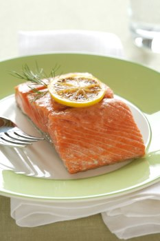Plate containing a serving of salmon topped with a slice of lemon. A fork is resting to the side.