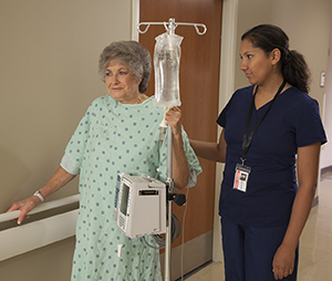 Healthcare provider walking with woman in hospital hallway.